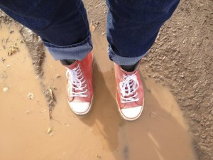 converse-style rubber boots in mud puddle